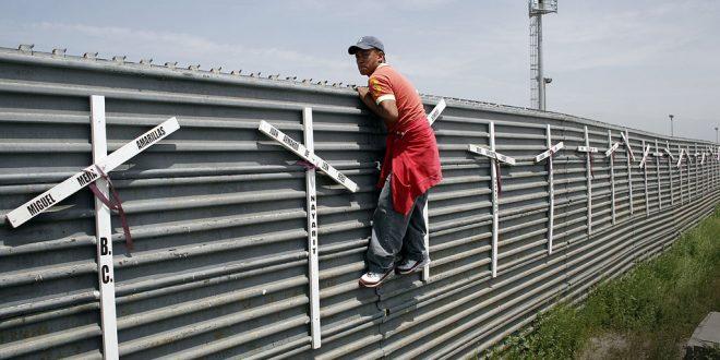 Migrante en el muro de Estados Unidos