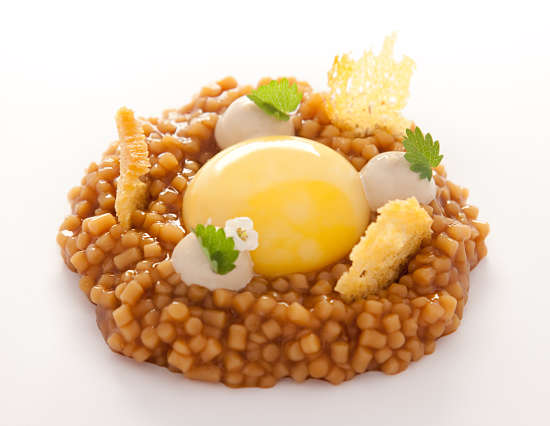 Yema de huevo de caserío sobre estofado de trigo y jugo de pimientos asados al carbón