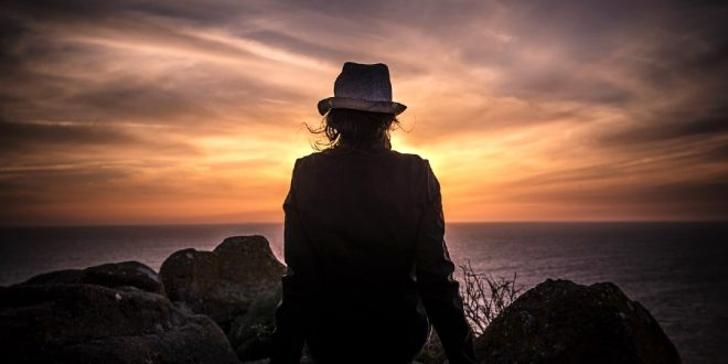 Mujer con sombrero viendo al horizonte