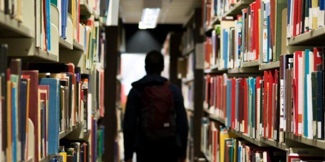 Estudiante de espaldas en el pasillo de una biblioteca