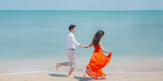 Pareja caminando feliz en la playa