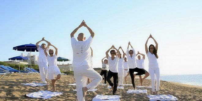 Gente en playa practicando turismo wellness