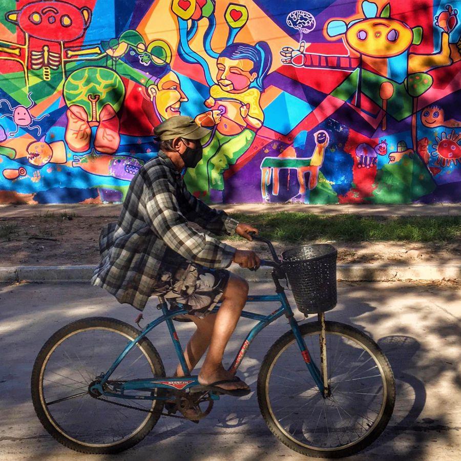 Señor en Bici, al fondo un Mural en Puerto Tirol